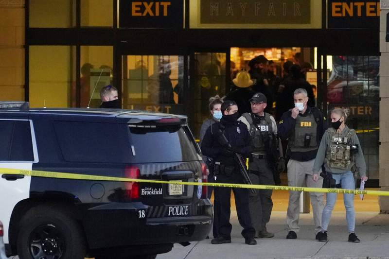 FBI officials and police stand outside the Mayfair Mall after a shooting, Friday, Nov. 20, 2020, in Wauwatosa, Wis. (AP Photo/Nam Y. Huh)