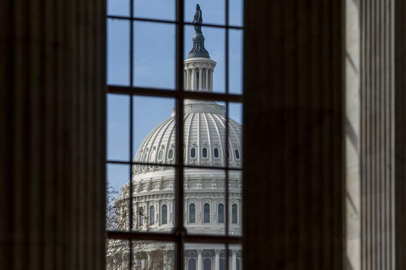 The Capitol is framed through a window in the Russell Senate Office Building as lawmakers negotiate on the emergency coronavirus response legislation, at the Capitol in Washington, Wednesday, March 18, 2020. (AP Photo/J. Scott Applewhite)
