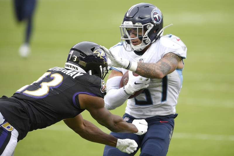Baltimore Ravens wide receiver Devin Duvernay, left, tries to bring down Tennessee Titans safety Amani Hooker after he intercepted a pass from Ravens quarterback Lamar Jackson during the second half of an NFL football game, Sunday, Nov. 22, 2020, in Baltimore. (AP Photo/Nick Wass)