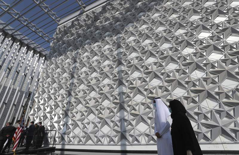 FILE - In this Nov. 18, 2020 file photo, people walk past the U.S.A Pavilion at the site of Dubai Expo 2020, in Dubai, United Arab Emirates. The UAE has relaxed and removed a range of limits on foreign ownership of companies, state-run media reported Monday, Nov. 23, 2020, in the countrys latest bid to boost its global status and attract foreign investors. The dramatic changes come as the UAE has spent billions of dollars preparing to host some 25 million visitors for the World Expo, which was pushed to 2021 due to the pandemic. (AP Photo/Kamran Jebreili, File)