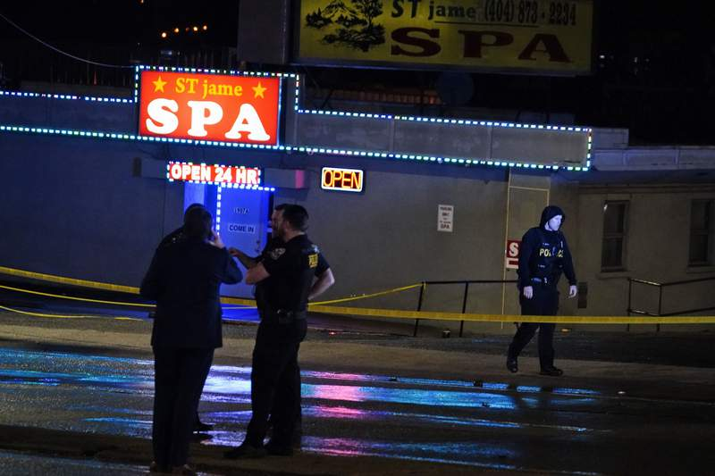 Law enforcement officials confer outside a massage parlor following a shooting on Tuesday, March 16, 2021, in Atlanta. Shootings at two massage parlors in Atlanta and one in the suburbs have left seven people dead, many of them women of Asian descent, authorities said Tuesday.   (AP Photo/Brynn Anderson)