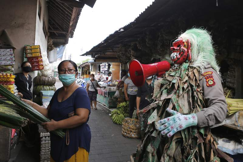 FILE - In this May 14, 2020, file photo, an Indonesian police officer wearing a Balinese traditional mask called 'celuluk', performs during a campaign calling for people to wear masks to curb the spread of coronavirus outbreak, at a market in Bali, Indonesia. A U.S.-based YouTuber and a Russian influencer were ordered off Indonesia's resort island of Bali on Friday after recording themselves defying mandatory mask-wearing with some imaginative makeup. Although first-time violators of Bali's mask-wearing rule face fines of 1 million rupiah ($70) for foreigners and deportation after a second offense, the police wanted them removed off the island immediately for deliberately provoking in public to defy health guidelines. (AP Photo/Firdia Lisnawati, File)