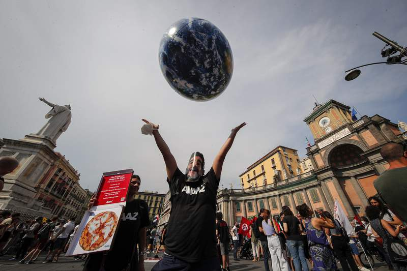FILE - In this Thursday, July 22, 2021 file photo, people demonstrate on the sidelines of a G20 environment meeting, in Naples, Italy. A coalition of environmental groups called Tuesday, Sept. 7, 2021 for this years climate summit to be postponed, arguing that too little has been done to ensure the safety of participants amid the continuing threat from COVID-19. The Climate Action Network, which includes more than 1,500 organizations in 130 countries, said there is a risk that many government delegates, civil society campaigners and journalists from developing countries may be unable to attend because of travel restrictions. The UN climate conference, known as COP26, is scheduled for early November in Scotland. (AP Photo/Salvatore Laporta, File)