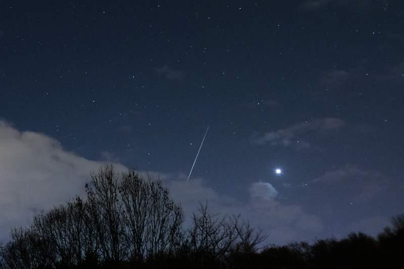 A meteor from a meteor shower streaks across the night sky.
