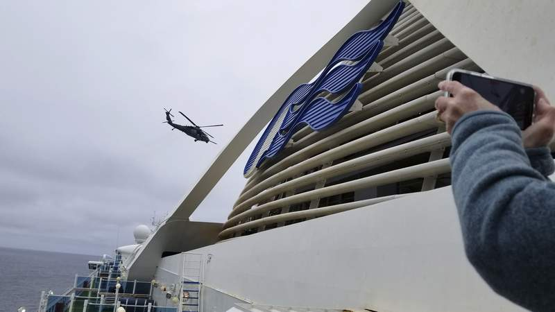 In this photo provided by Michele Smith, a Coast Guard helicopter delivering virus testing kits hovers above the Grand Princess cruise ship Thursday, March 5, 2020, off the California coast. Scrambling to keep the coronavirus at bay, officials ordered a cruise ship with about 3,500 people aboard to hold off the California coast Thursday until passengers and crew could be tested, after a traveler from its previous voyage died and at least one other became infected. Princess Cruises says fewer than 100 of those aboard have been identified for testing. (Michele Smith via AP)