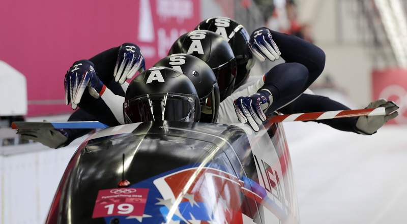 FILE - In this Feb. 25, 2018, file photo, driver Justin Olsen and Christopher Fogt, Carlo Valdes and Nathan Weber, of the United States, start their third heat during the four-man bobsled final at the Winter Olympics in Pyeongchang, South Korea. USA Bobsled and Skeleton couldn't hit the road recruiting this summer because of the coronavirus pandemic. So, they made Olympic hopefuls come to them and do so online. USABS took its recruiting process digital this year and team officials say it has led to significant upticks in interest. (AP Photo/Wong Maye-E, File)