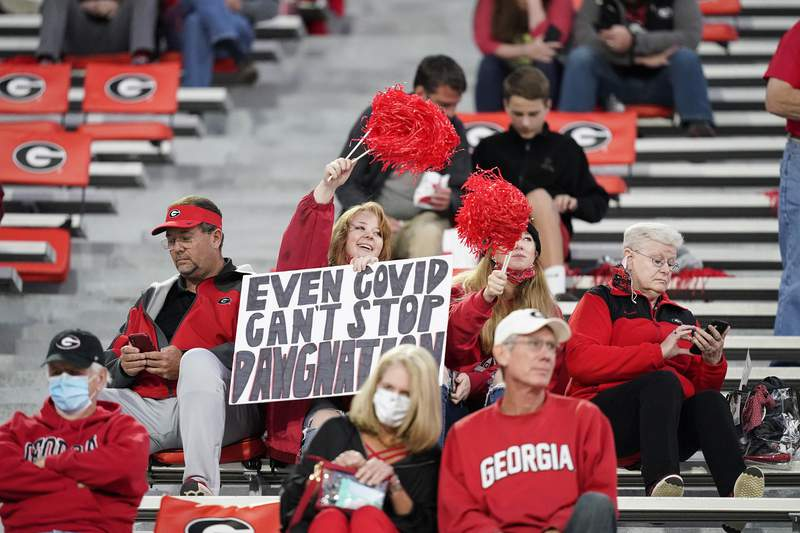 """FILE  - In this Oct. 3, 2020, file photo, a fan holds a sign """"Even COVID can't stop Dawgmation"""" before an NCAA college football game, in Athens, Ga. Coaches wearing masks around their chins. Fans not wearing masks at all while cheering from their seats. One school deciding to drop the safety checks it was requiring for those entering the stadium to cut down on long lines. College football is sending plenty of alarming signals at it attempts to get through a tenuous season amid a pandemic. (AP Photo/Brynn Anderson, File)"""