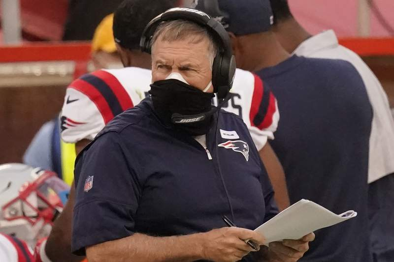 New England Patriots head coach Bill Belichick wears two masks as he watches from the sideline during the first half of an NFL football game against the Kansas City Chiefs , Monday, Oct. 5, 2020, in Kansas City. The New England Patriots have canceled practice amid reports that a third player has tested positive for the coronavirus.  Sports Illustrated reported that reigning NFL Defensive Player of the Year Stephon Gilmore tested positive for the virus on Wednesday, Oct. 7, 2020, and was added to the team's reserve/COVID-19 list. (AP Photo/Charlie Riedel)
