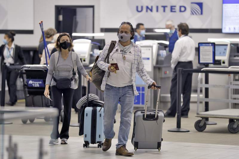 Passengers wearing personal protective face masks leave the United Airline ticket counter after checking at the Tampa International Airport in this file photo.