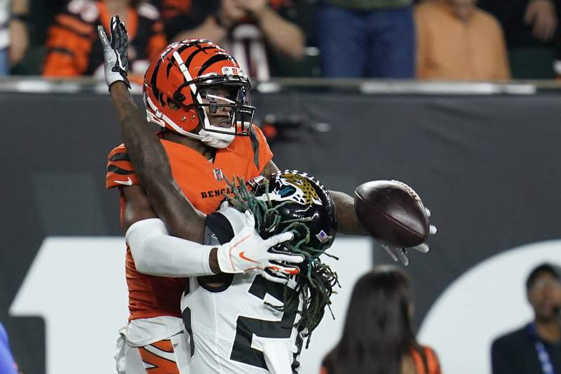 Jacksonville Jaguars' Shaquill Griffin (26) breaks up a pass intended for Cincinnati Bengals' Ja'Marr Chase (1) during the second half of an NFL football game, Thursday, Sept. 30, 2021, in Cincinnati. (AP Photo/Michael Conroy)