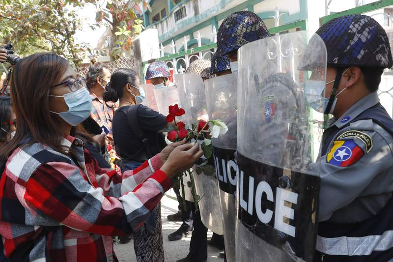 Supporters give roses to police while four arrested activists make a court appearance in Mandalay, Myanmar, Friday, Feb. 5, 2021. Hundreds of students and teachers have taken to Myanmar's streets to demand the military hand power back to elected politicians, as resistance to a coup swelled with demonstrations in several parts of the country. (AP Photo)