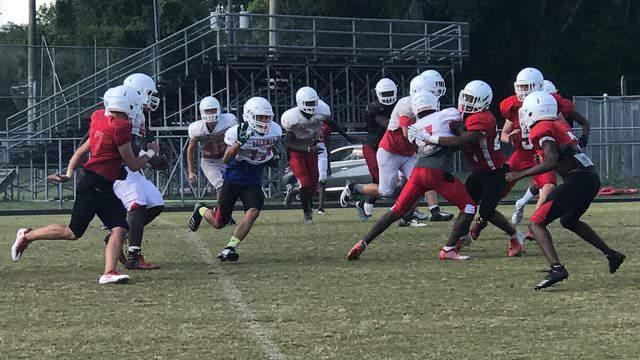 Baldwin football players run a play at spring practice on April 30.