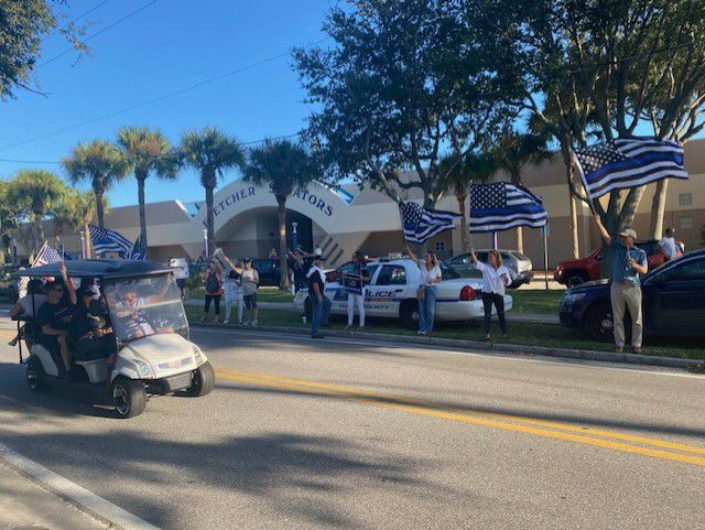 With Thin Blue Line flags & signs, dozens gather outside Fletcher High School
