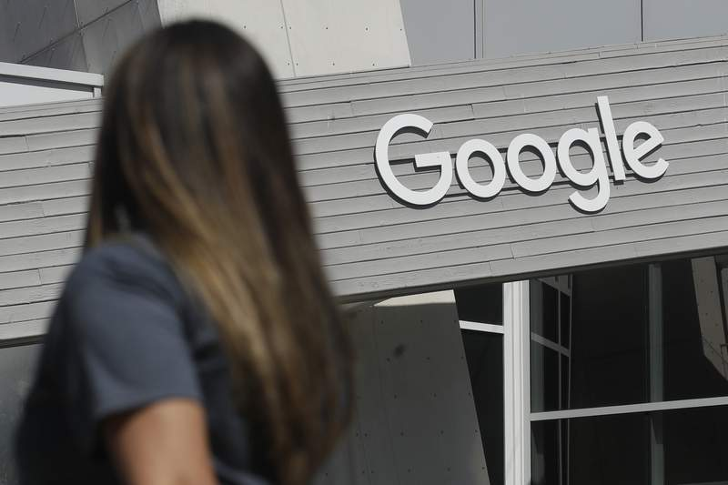 FILE - In this Sept. 24, 2019, file photo, a woman walks below a Google sign on the campus in Mountain View, Calif.  Google on Thursday, Oct. 7, 2021, will no longer allow digital ads promoting false climate change claims to appear next to the content of other publishers, hoping to deny money to those making such claims and to stop the spread of misinformation on its platform.   (AP Photo/Jeff Chiu, File)