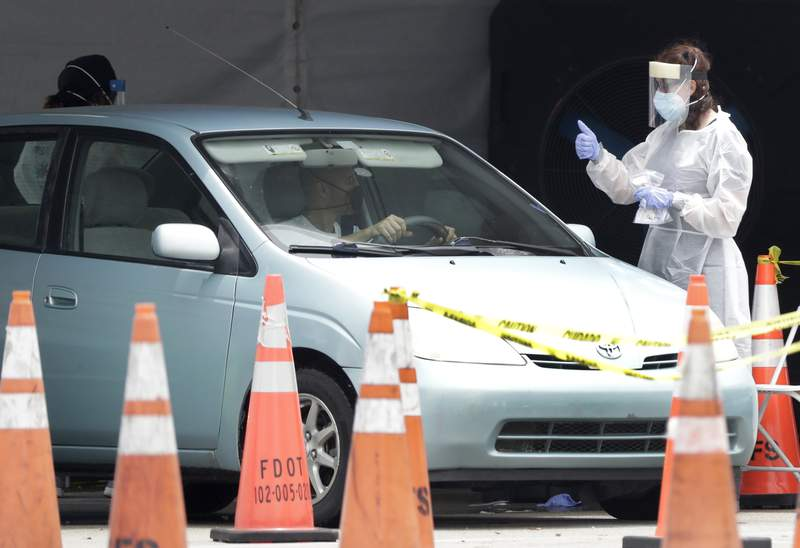A healthcare worker gives a thumbs up to a driver as he stops his car at a COVID-19 testing site outside Hard Rock Stadium in Miami Gardens.