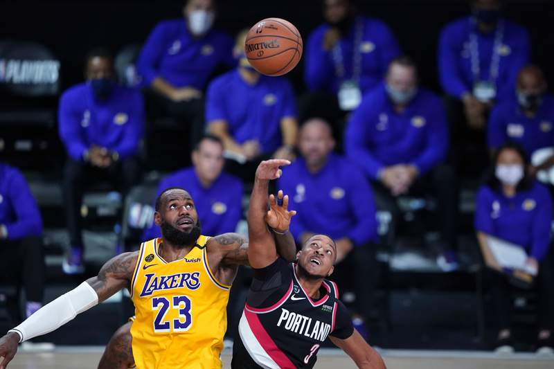 Los Angeles Lakers forward LeBron James (23) and Portland Trail Blazers guard CJ McCollum (3) battle for possession during the second half of an NBA basketball game Tuesday, Aug. 18, 2020, in Lake Buena Vista, Fla. (AP Photo/Ashley Landis, Pool)