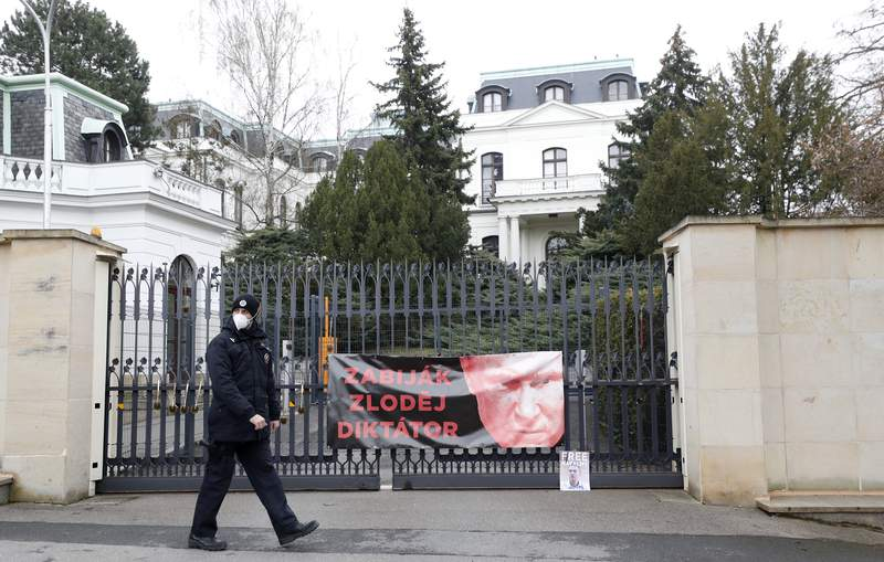 """A policeman walks by a poster attached by protesters to a gate of the Russian embassy in Prague, Czech Republic, Friday, April 16, 2021. Czech Republic is expelling 18 diplomats identified as spies over a 2014 ammunition depot explosion. On Saturday, April 17, 2021, Prime Minister Andrej Babis said the Czech spy agencies provided clear evidence about the involvement of Russian military agents in the massive explosion that killed two people. The poster depicting Russian President Vladimir Putin reads: """"Killer, Thief, Dictator"""". (AP Photo/Petr David Josek)"""