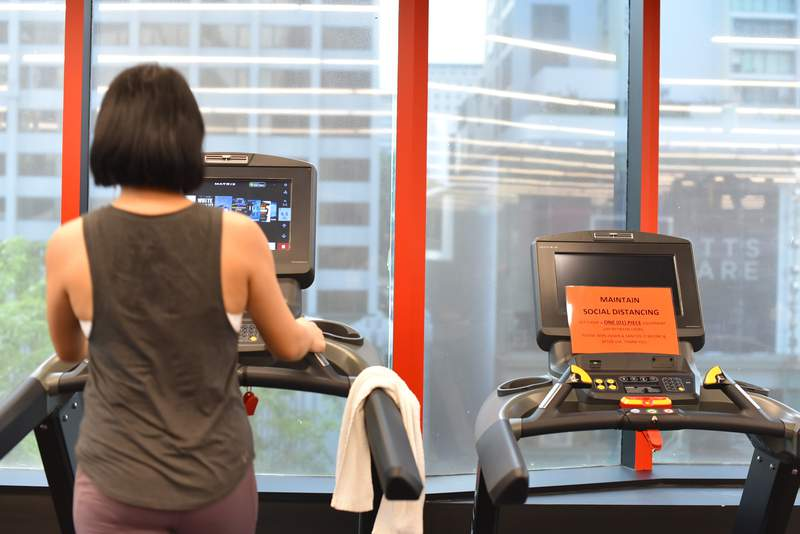 A sign that reads maintain social distancing is mounted on a vacant treadmill beside a woman at a fitness center Friday, June 19, 2020, in Singapore. Singaporeans now can wine and dine at restaurants, work out at the gym and get together with up to five people after most lockdown restrictions were lifted Friday. (AP Photo/YK Chan)
