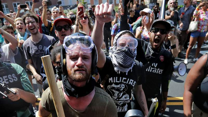 """Anti-fascist counter-protesters wait outside Lee Park to hurl insults as white nationalists, neo-Nazis and members of the """"alt-right"""" are forced out after the """"Unite the Right"""" rally was declared an unlawful gathering August 12, 2017 in Charlottesville, Virginia. As protests over George Floyd's death spread across the country, officials have blamed the violent nature of some demonstrations on members of a controversial group known as Antifa. (Chip Somodevilla/Getty Images)"""