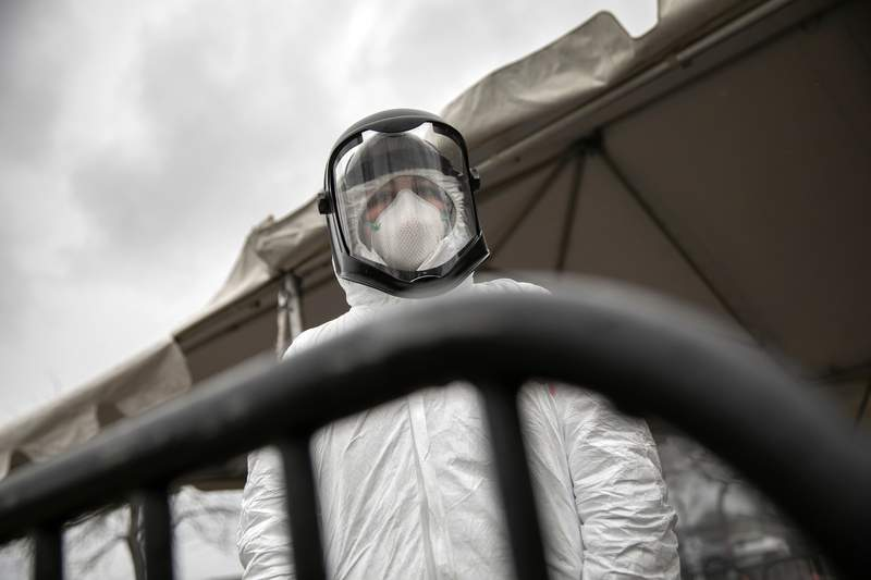 Nurse Hannah Sutherland, dressed in personal protective equipment (PPE) awaits new patients at a drive-thru coronavirus testing station