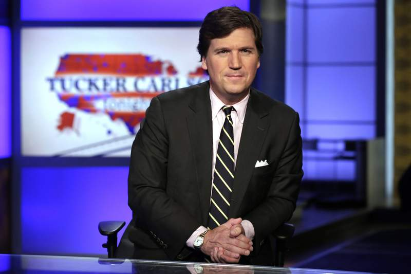"""FILE - In this March 2, 2017 file photo, Tucker Carlson, host of """"Tucker Carlson Tonight,"""" poses for photos in a Fox News Channel studio, in New York. Carlson says he felt a moral obligation to meet with President Donald Trump to warn him about the seriousness of coronavirus. He told Vanity Fair that while he didn't feel it was his role, his wife convinced him to request the meeting, which took place on March 7. (AP Photo/Richard Drew, File)"""