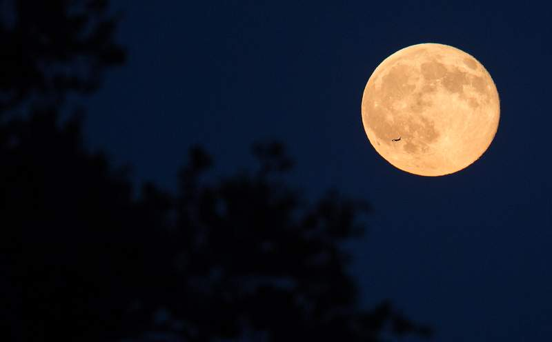 A plane is seen flying in front of the second full moon for the month of July, Friday, July 31, 2015 in Arlington, Va. In recent years, people have been using the name Blue Moon for the second of two full moons in a single calendar month. An older definition of Blue Moon is that it's the third of four full moons in a single season.  Photo Credit: (NASA/Joel Kowsky)