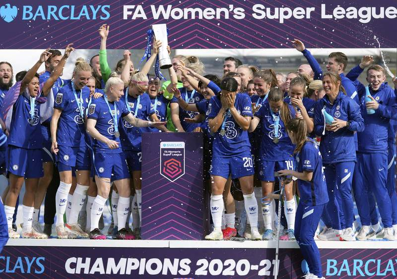 Chelsea players celebrate with the Women's Super League trophy at Kingsmeadow, London, Sunday, May 9, 2021. Chelsea retained the Womens Super League title and became the all-time record champion in the English game by beating Manchester City to first place. Chelsea was a 5-0 winner at home to Reading and finished two points ahead of City. (John Walton/PA via AP)