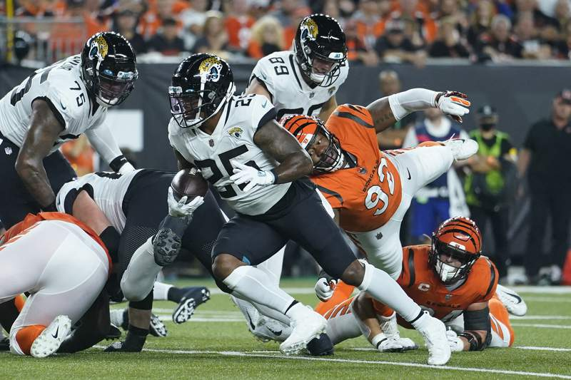 Jacksonville Jaguars' James Robinson (25) runs for a touchdown past Cincinnati Bengals' B.J. Hill (92) during the first half of an NFL football game, Thursday, Sept. 30, 2021, in Cincinnati. (AP Photo/Michael Conroy)
