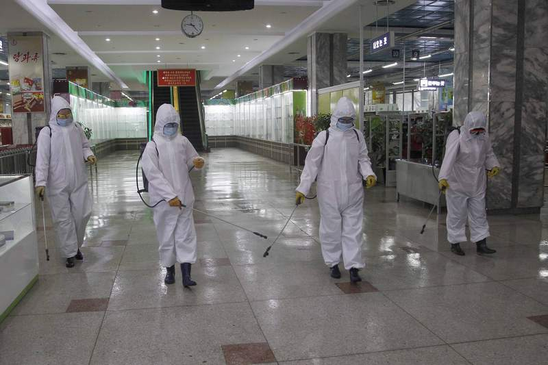FILE - In this Dec. 28, 2020, file photo, staff of the Pyongyang Department Store No. 1 disinfect the store to help curb the spread of the coronavirus before it opens in Pyongyang, North Korea. The World Health Organization says it has started a process of sending COVID-19 medical supplies to North Korea through the Chinese port of Dalian, a possible sign that the North is easing one of the worlds toughest pandemic border closures to receive outside help.(AP Photo/Jon Chol Jin, File)