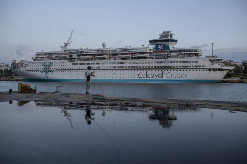 A man fishes in front of a docked cruise ship in Piraeus port, near Athens, Greece,