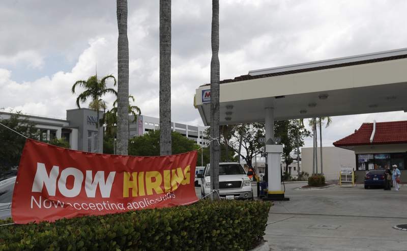 FILE - In this, Wednesday, May 6, 2020 photo, a now hiring sign is displayed on a street corner in North Miami Beach, Fla. (AP Photo/Wilfredo Lee)
