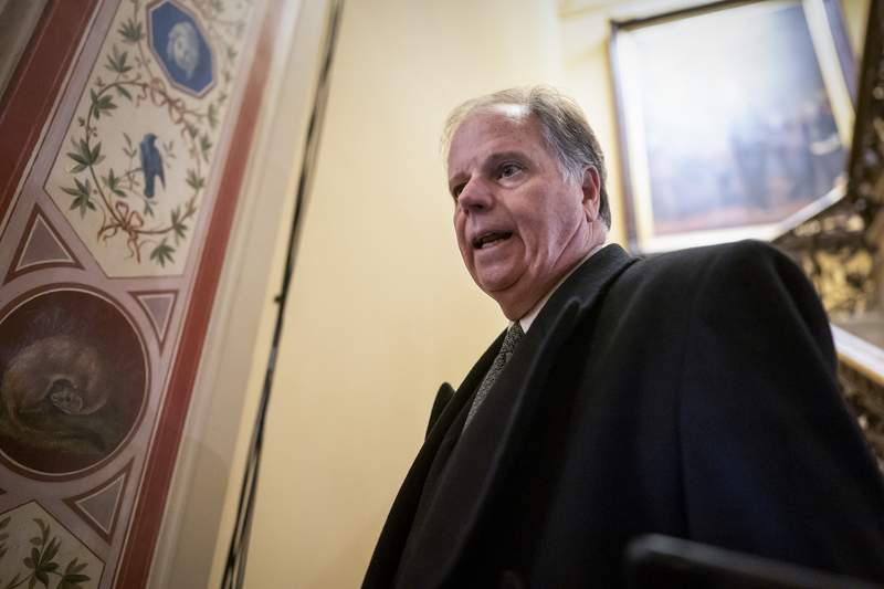 FILE - In this Jan. 31, 2020 file photo, Sen. Doug Jones, D-Ala., is questioned by reporters as he arrives at the Capitol for the impeachment trial of President Donald Trump on charges of abuse of power and obstruction of Congress, in Washington.   Jones, the most endangered Democrat in this November's elections, said Wednesday that he will vote to convict President Donald Trump Wednesday as the Senate impeachment trial reaches its climax. (AP Photo/J. Scott Applewhite)