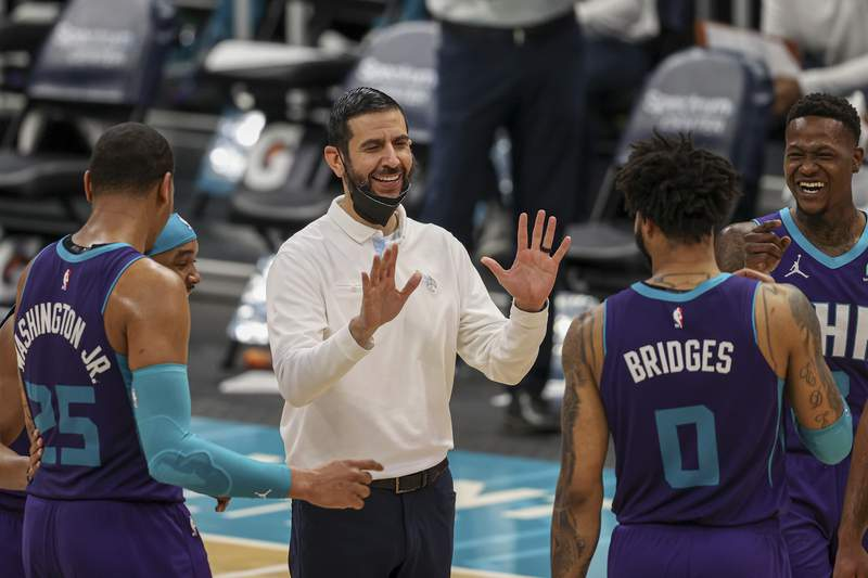 FILE - Charlotte Hornets coach James Borrego, center, laughs with Charlotte Hornets Devonte' Graham, P.J. Washington, Miles Bridges and Terry Rozier during an NBA basketball game against the Atlanta Hawks in Charlotte, N.C., in this Sunday, April 11, 2021, file photo. The Charlotte Hornets have agreed to a multiyear contract extension with coach James Borrego, according to a person with knowledge of the situation.  Borrego is expected to sign the deal Monday, Aug. 9, 2021. The person spoke to The Associated Press on condition of anonymity because the team has not yet announced the extension. (AP Photo/Nell Redmond, File)