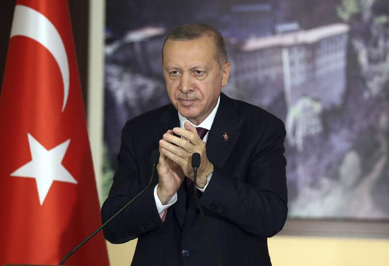 Turkey's President Recep Tayyip Erdogan applauds during a conference in Istanbul, Tuesday, July 28, 2020. Turkish lawmakers were making their final speeches Tuesday before voting on a bill that would give the government greater powers to regulate social media, in what human rights groups and the opposition have decried as a violation of free expression online. Hundreds of social media users have already been investigated and some arrested for their posts on the COVID-19 pandemic, opposition to Turkish military offensives in Syria or insulting Erdogan and other officials. (Turkish Presidency via AP, Pool)