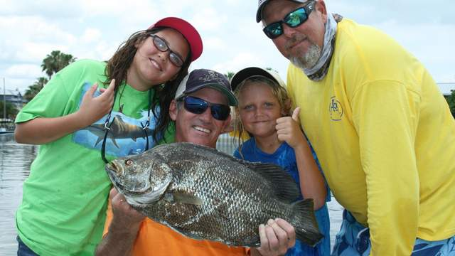 Capt Don Dingman, of Hook The Future TV with Capt Joel Brandenburg and two junior anglers showing off a tripletail catch.