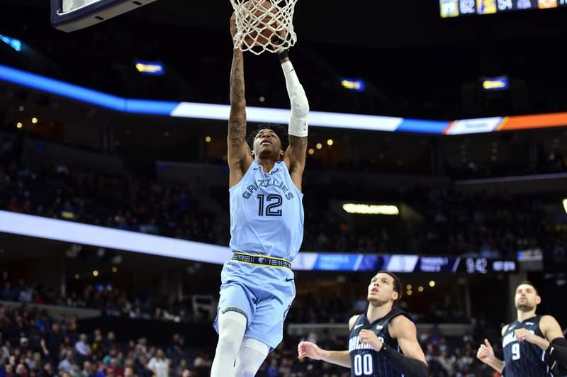 Memphis Grizzlies guard Ja Morant (12) dunks ahead of Orlando Magic forward Aaron Gordon (00) and center Nikola Vucevic (9) during the first half of an NBA basketball game Tuesday, March 10, 2020, in Memphis, Tenn. (AP Photo/Brandon Dill)