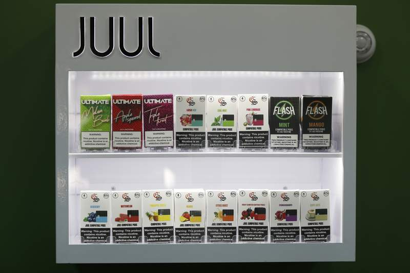 FILE - In this Sept. 3, 2019, file photo, electronic cigarette pods are displayed for sale at a shop, in Biddeford, Maine. Vaping giant Juul Labs has donated thousands of dollars to court state attorneys general. But the lobbying strategy may be backfiring. (AP Photo/Robert F. Bukaty, File)