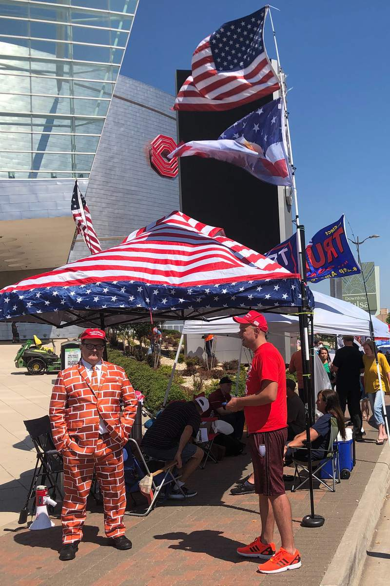 Supporters of President Trump, including a man dressed as the border wall, line up outside outside an arena in Tulsa, Oklahoma, June 18, 2020, where the president will hold his first campaign rally in months this weekend .Despite the heat, the ever-growing risk of coronavirus and a lukewarm reception from local officials, dozens of backers of Trump are already camped out outside the arena (AP photo/ Tom McCarthy)