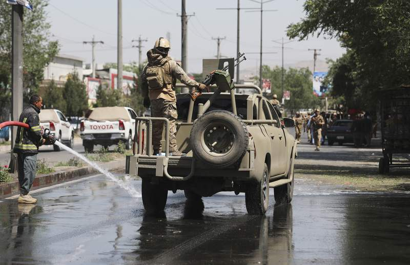 In this June 6, 2021, photo, Afghan security personnel leave the scene of a roadside bomb explosion in Kabul, Afghanistan. The U.S. withdrawal from Afghanistan is more than half done, and U.S. officials say that while it could be completed by July 4, the final exit of equipment and troops more likely will be later in the summer. (AP Photo/Rahmat Gul)