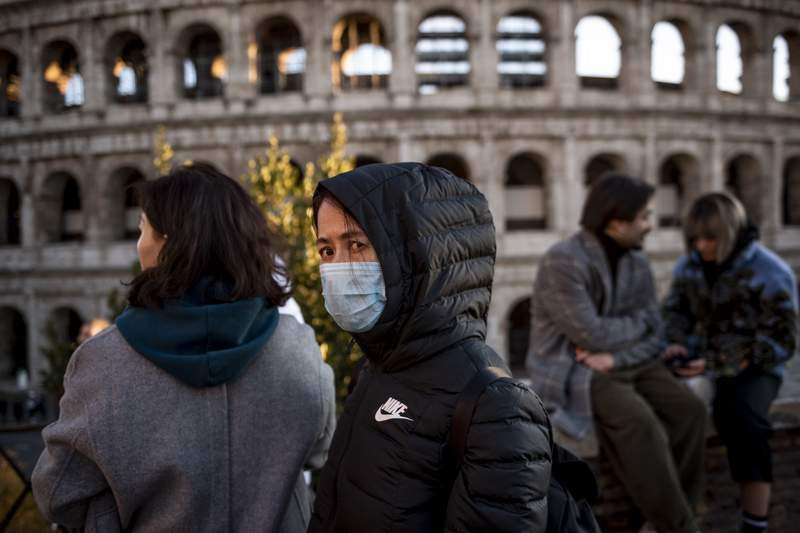 Chinese tourists wearing face masks visit the Colosseum area on February 6, 2020 in Rome, Italy.