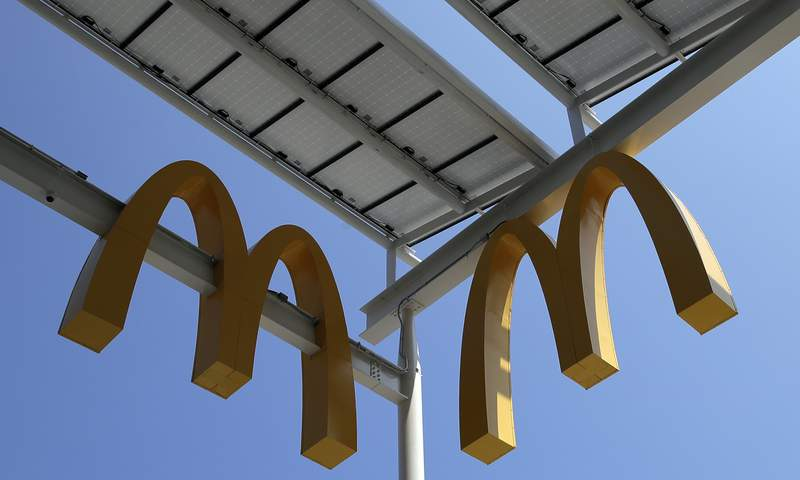 FILE- This Aug. 8, 2018, photo shows logos of McDonald's Chicago flagship restaurant. McDonalds is raising pay at 650 company-owned stores in the U.S. as part of its push to hire thousands of new workers in a tight labor market. The fast food giant is the latest restaurant chain to announce pay raises. (AP Photo/Nam Y. Huh, File)