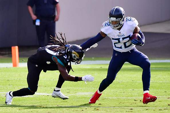 Yulee High School graduate Derrick Henry of the Tennessee Titans stiff arms Tre Herndon of the Jacksonville Jaguars at TIAA Bank Field on December 13, 2020 in Jacksonville, Florida. (Photo by Julio Aguilar/Getty Images)