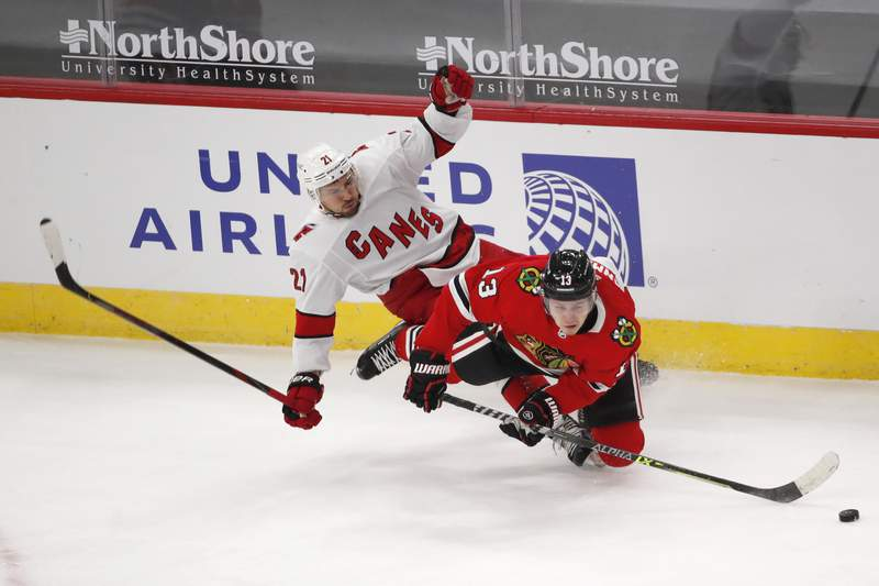 Carolina Hurricanes right wing Nino Niederreiter (21) trips over Chicago Blackhawks center Mattias Janmark (13) as they battle for the puck during the second period of an NHL hockey game Thursday, April 1, 2021, in Chicago. (AP Photo/Jeff Haynes)