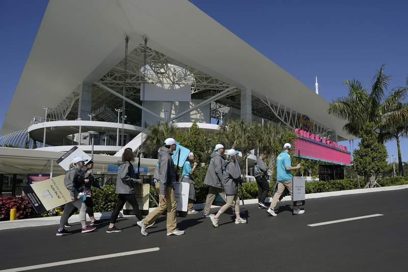 Workers arrive outside of the Hard Rock Stadium before the NFL Super Bowl 54 football game between the San Francisco 49ers and the Kansas City Chiefs, Sunday, Feb. 2, 2020, in Miami. (AP Photo/David J. Phillip)