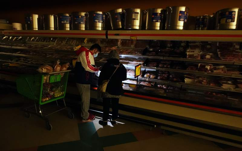 FILE - In this Tuesday, Feb. 16, 2021 file photo, customers use the light from a cell phone to look in the meat section of a grocery store that was without power, in Dallas. Brazos Electric Power Cooperative Inc., the oldest and biggest generation and transmission power cooperative in Texas has filed for Chapter 11 bankruptcy protection following last months winter storm that left millions without power.  (AP Photo/LM Otero, File)