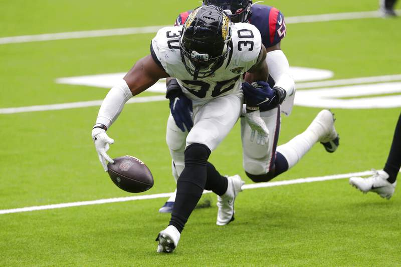 Jacksonville Jaguars running back James Robinson fumbles as he is hit by Houston Texans linebacker Tyrell Adams during their game on Oct. 11 in Houston.