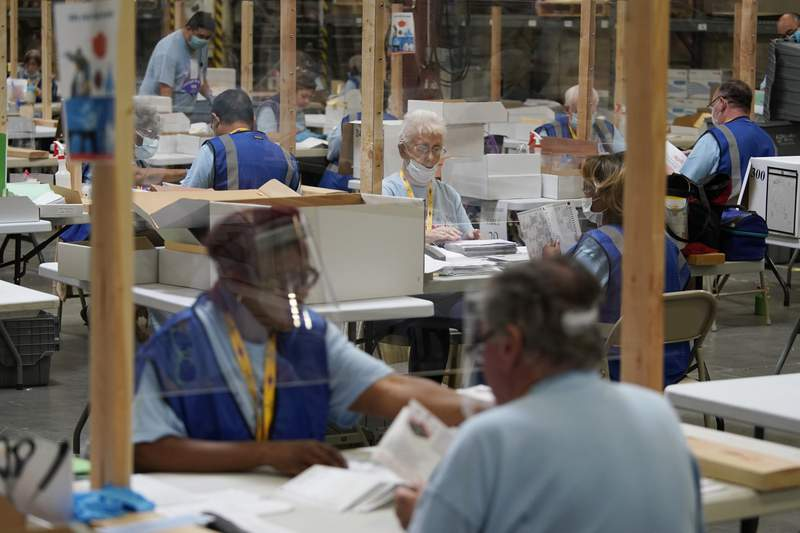 File photo of election workers processing mail-in ballots.