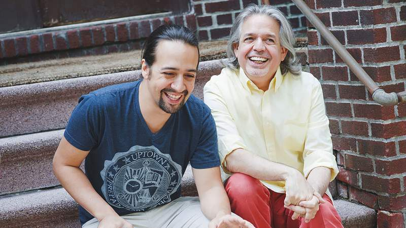 In this undated photo provided by Monica Simoes, Lin-Manuel Miranda, left, laughs with his father Luis Miranda Jr.  The award-winning Hamilton creator says the inspirations for his art and philanthropy are linked. With a series of donations to organizations helping immigrants announced Tuesday, July 6, 2021, Miranda and his familys nonprofit will support the new focus on immigration in the movie version of his musical In the Heights.   (Monica Simoes via AP)
