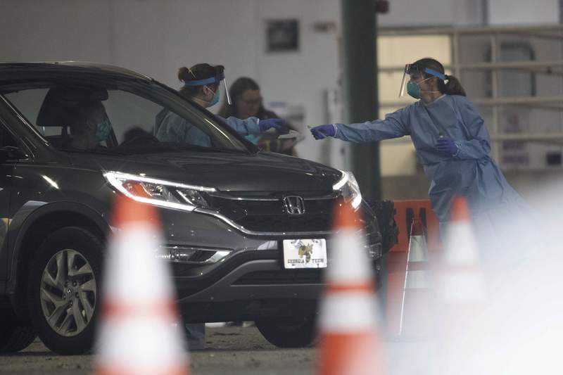 A person is given a test for COVID-19 at a drive through testing location Wednesday, March 18, 2020, in Marietta, Ga. The testing is not open to the public people must be referred by the health department. (AP Photo/John Bazemore)