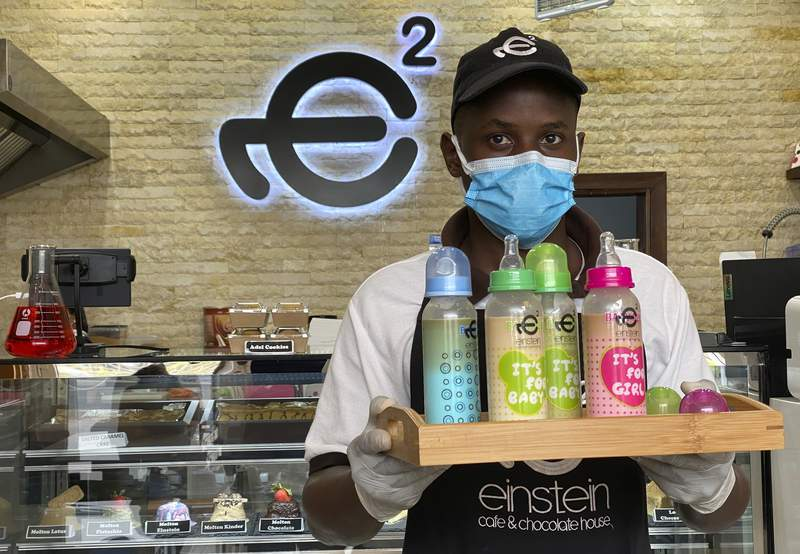 A waiter poses with a tray of baby bottles that he brought out from storage, at Einstein Cafe in Dubai, United Arab Emirates, Sunday, March 14, 2021. Cafes across several Gulf Arab states have begun selling coffee and other cold drinks in baby bottles, kicking off a new trend that has prompted excitement, confusion and backlash. The fad started at Einstein Cafe, a slick dessert chain with branches across the region. Soon, authorities from Kuwait to Dubai cracked down claiming the trend violates local traditions.(AP Photo/Kamran Jebreili)